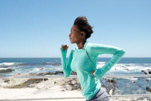 Une femme noire qui court en bordure de mer, les écouteurs dans les oreilles
