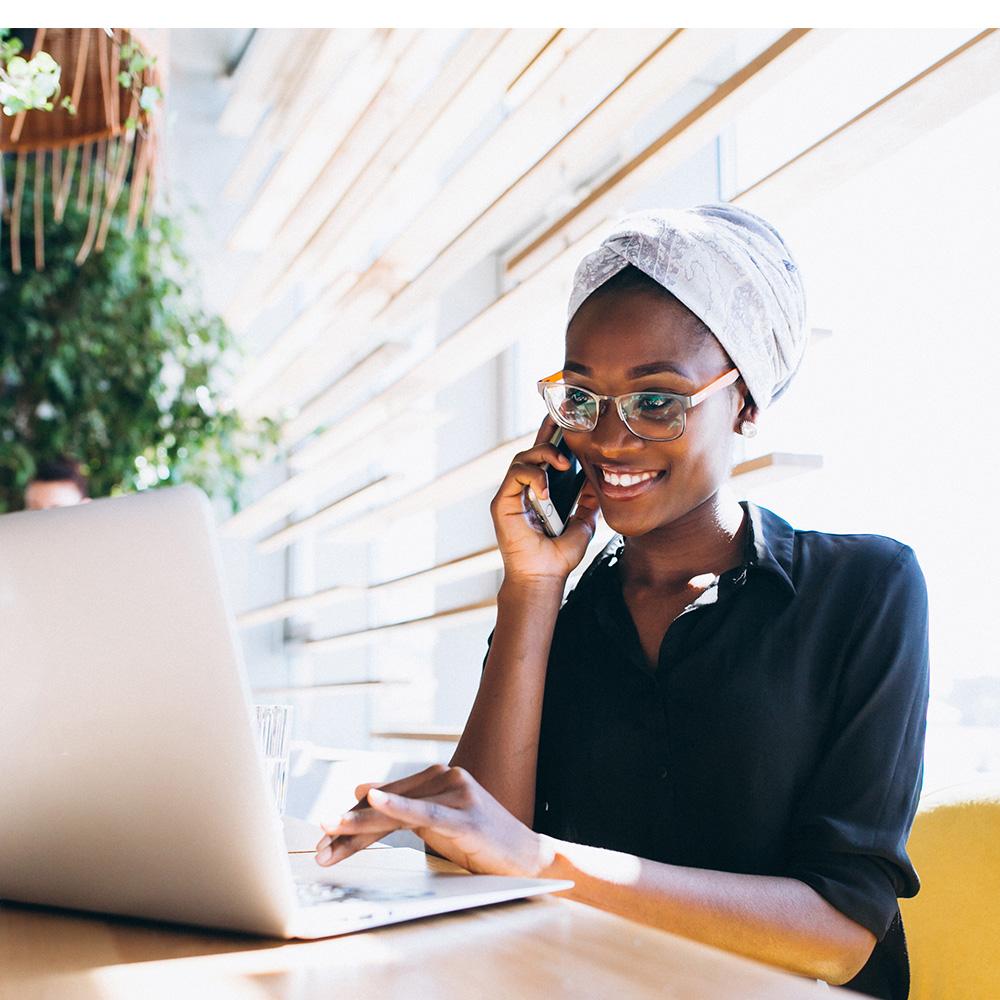 femme africaine ayana souriante au téléphone et en télétravail sur son ordinateur