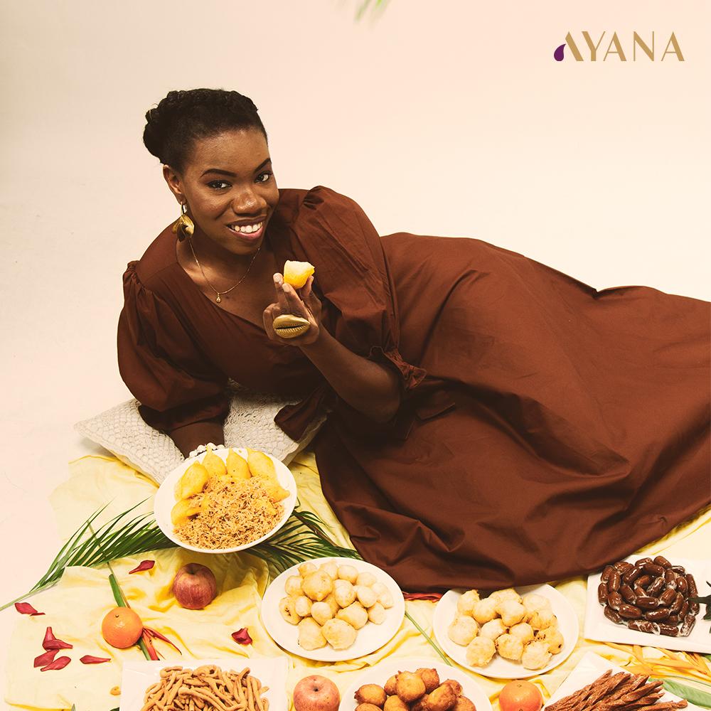 Tatou Dembélé, fondatrice d'Ivorian Food et cover girl du Mini Mag AYANA n°3 devant plusieurs plats ivoiriens